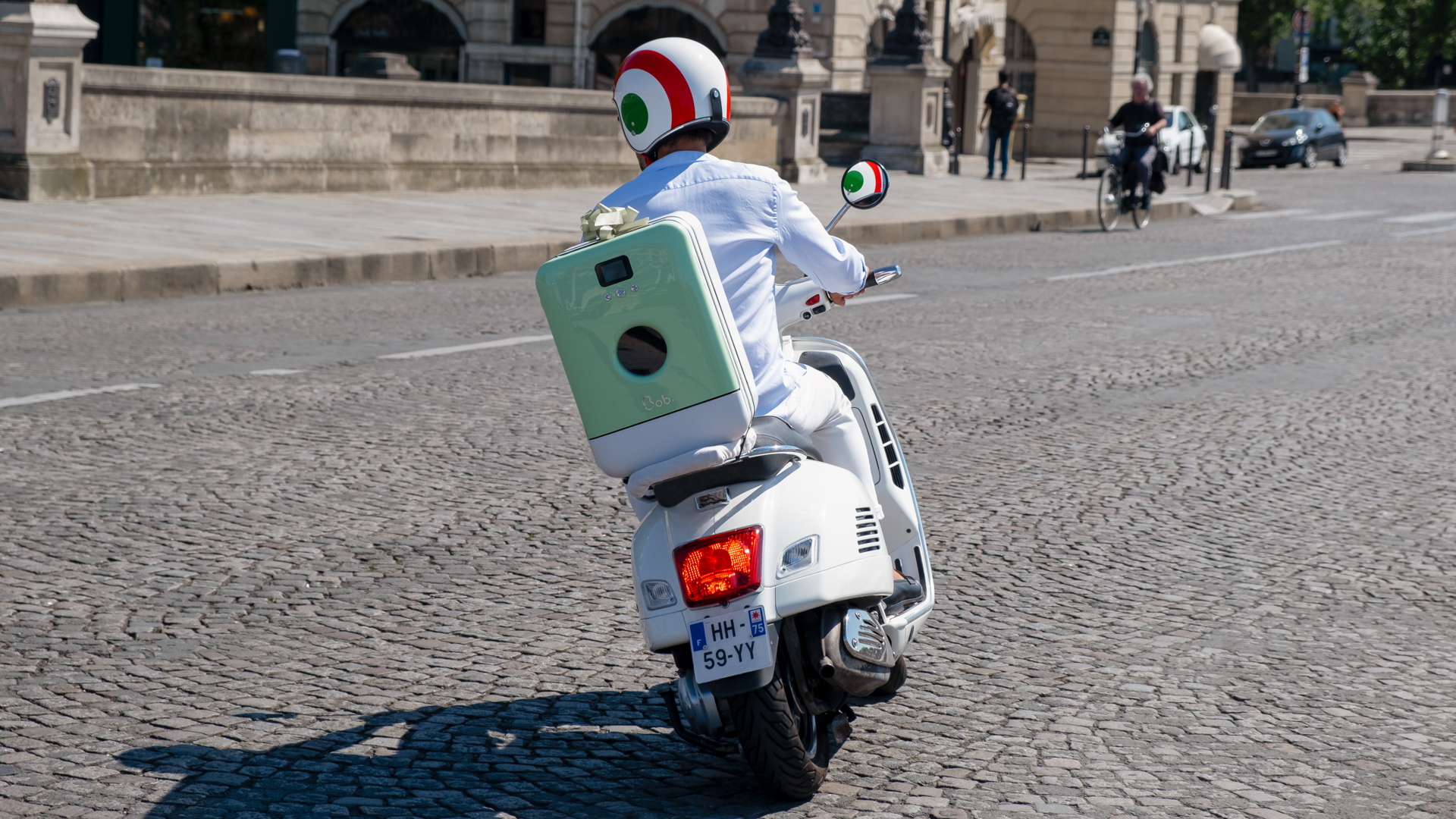 Bob le mini lave vaisselle sur un scooter Vespa avec casque drapeau italien à Paris